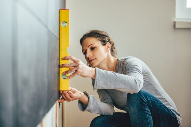 Woman wearing grey shirt using leveling tool at home